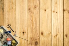 La caja de sastre, scissor, cinta métrica y los hilos de coser con las bobinas coloridas para el remiendo en fondo de madera foto de archivo