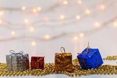 La caja del Año Nuevo con un regalo en una falta de definición del fondo se enciende Imagenes de archivo