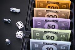 La caja del juego de mesa del monopolio con el dinero embala, los símbolos y corta en cuadritos Imagenes de archivo