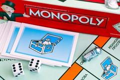 La caja del juego de mesa del monopolio, tarjetas del pecho de comunidad, símbolos, corta en cuadritos encendido Imagen de archivo libre de regalías