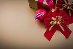 La caja del presente de la bola de la Navidad con la cinta atada arquea Fotos de archivo libres de regalías