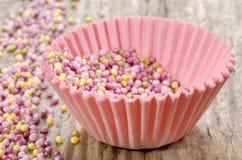 La caja rosada de la magdalena con el az?car asperja Imagenes de archivo