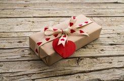 La caja y el corazón de regalo de la tarjeta del día de San Valentín forman la etiqueta en el tablero de madera Imagen de archivo libre de regalías