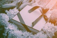 La caja y las flores de regalo enmarcan el backbround en un backgrou de madera del piso Fotos de archivo