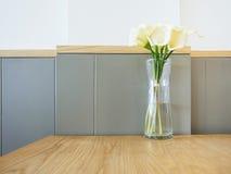 La cala blanca florece en el florero de cristal en la tabla Fotos de archivo