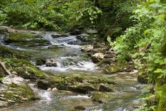 La cala dulce fluye entre dos colinas escarpadas Fotografía de archivo