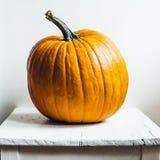 La calabaza anaranjada brillante en viejo blanco pintó la silla de madera Foto de archivo libre de regalías