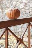 La calabaza anaranjada grande miente en la verja de madera del mirador Imagenes de archivo