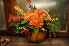 La calabaza con un ramo hermoso de otoño florece dentro Fotografía de archivo libre de regalías