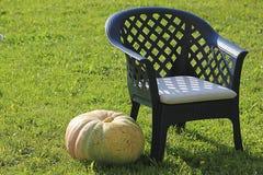 La calabaza está al lado de silla del país en hierba verde Imagen de archivo libre de regalías
