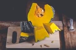 La calabaza tailandesa cruda cortó mitad en la tabla de madera Fotografía de archivo
