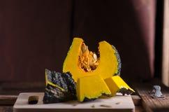 La calabaza tailandesa cruda cortó mitad en la tabla de madera Foto de archivo