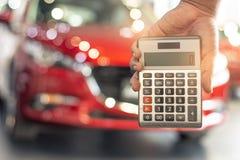 La calculadora asi?tica de la tenencia del hombre para las finanzas del negocio en la sala de exposici?n del coche empa?? el fond imagenes de archivo