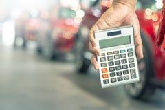 La calculadora asi?tica de la tenencia del hombre para las finanzas del negocio en la sala de exposici?n del coche empa?? el fond foto de archivo