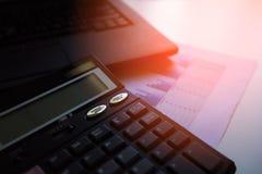 La calculadora con los gráficos de negocio y las cartas divulgan sobre la tabla, calculadora en el escritorio del cepillado finan Imágenes de archivo libres de regalías