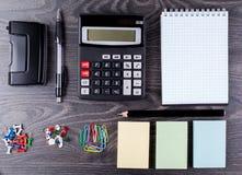La calculadora, cuaderno, prospectos para el expediente y efectos de escritorio Fotos de archivo