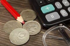 La calculadora, el lápiz rojo, las monedas viejas de la URSS y los vidrios mienten en una tabla de madera Primer Foco selectivo Foto de archivo