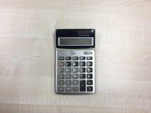 La calculadora en la tabla de madera Fotos de archivo libres de regalías