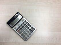 La calculadora en la tabla de madera Fotos de archivo