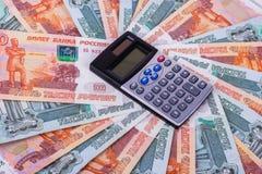 La calculadora está en fondo del dinero Imagen de archivo libre de regalías