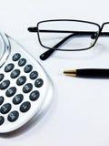 La calculadora, la pluma y los vidrios se cierran para arriba Fotos de archivo