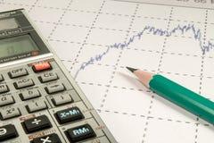 La calculadora y el lápiz acuña en graffica a Dow Jones Imagen de archivo