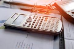 La calculatrice avec des graphiques de gestion et les diagrammes rendent compte de tabble, calculatrice sur le bureau du rabotage Image libre de droits