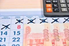 La calculatrice et les billets de banque de cinq mille roubles sont sur le cale Photo libre de droits