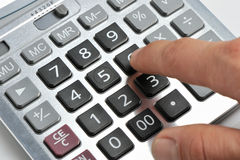 La calculatrice et une main de l'homme Photographie stock libre de droits