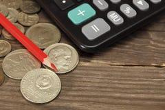 La calculatrice, le crayon rouge et les vieilles pièces de monnaie de l'URSS se trouvent sur une table en bois Plan rapproché Foy Photos stock
