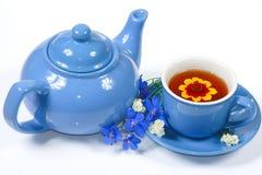 La caldaia e la tazza blu di tè con i fiori Immagine Stock
