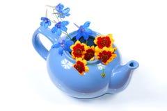 La caldera azul con las flores anaranjadas y azules Imagen de archivo libre de regalías