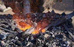 La calefacción del metal aloja en los carbones calientes Foto de archivo
