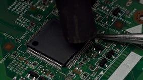 La calefacción del microchip entra en contacto con en la placa de circuito impresa electrónica que usa la estación que suelda Sup almacen de metraje de vídeo
