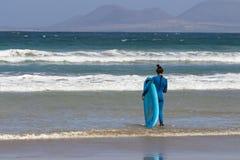 La Caleta, Spanien, Mädchen des Surfers 03-14-2019, das in die Wellen an La Caleta-Strand geht Lanzarote stockfoto