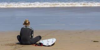 La Caleta, Spanien, Mädchen des Surfers 03-14-2019, das an La Caleta-Strand sitzt Lanzarote Kanarische Inseln lizenzfreies stockbild