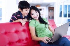 La calidad de la madre y del hijo mide el tiempo en casa en el sofá rojo Imagenes de archivo