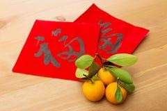 La caligrafía china y el kumquat, significado del Año Nuevo de la palabra es buen l Foto de archivo