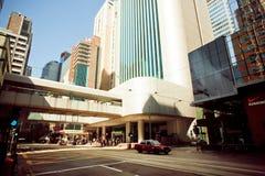 La calle amplia oscura con los rascacielos y ayuna conduciendo el coche del taxi en el camino de ciudad de Hong Kong Fotografía de archivo