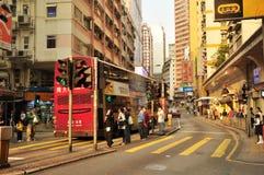 La calle comercial el autobús de dos capas y los transeúntes en la calle de Hong Kong ve en central Foto de archivo libre de regalías
