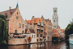 La calle en Brujas Bélgica cruzó por el río Zwyn con tres cisnes, pasando por alto la torre de reloj imagen de archivo libre de regalías