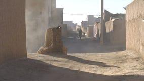 La calle tiró el callejón en pueblo de la arcilla en Marruecos, África Un hombre en djellaba usando la manguera del agua para sup metrajes