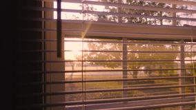 La calle tranquila de la salida del sol de la mañana a través de persianas de ventana se cierra para arriba