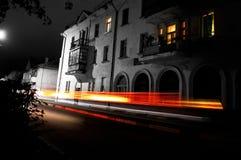 La calle vacía de la noche de una ciudad europea con las pequeñas casas, coche se enciende en la falta de definición Fotos de archivo libres de regalías