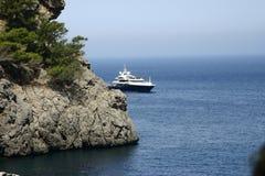 La Calobra beach at the spanish island Mallorca. Scenic view of modern motorized yacht sailing around rock mediterranean coastline Royalty Free Stock Photo