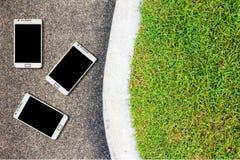 La calzada concreta en el parque tiene un teléfono celular en el piso Foto de archivo libre de regalías