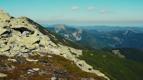 La caméra adopte la position panoramique de la crête de la gamme de montagne carpathienne Une vue des pentes boisées et de falais banque de vidéos