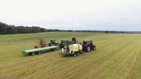 La caméra de bourdon montre le grand champ avec quatre types de machines agricoles là-dessus banque de vidéos