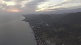 La caméra de bourdon montre la Mer Noire, la ligne de côte, colline verte au coucher du soleil avec le ciel nuageux banque de vidéos