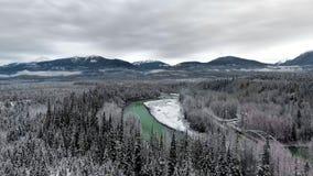 La caméra de drone se déplace au-dessus d'une épaisse forêt enneigée avec un étang émeraude et une autoroute près des montagnes p banque de vidéos